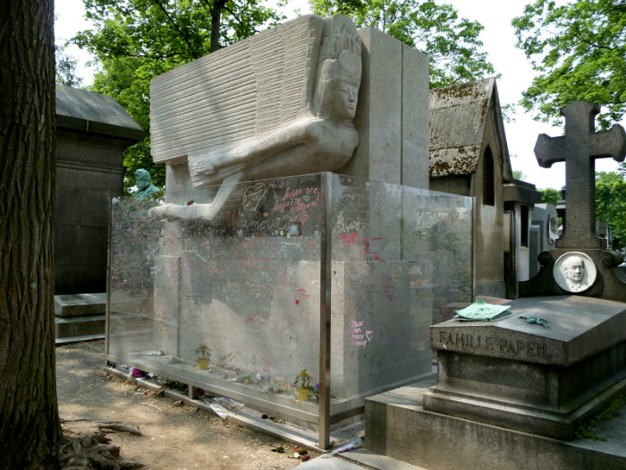 The tomb of Oscar Wilde with the protective glass barrier by Agateller, Public Domain