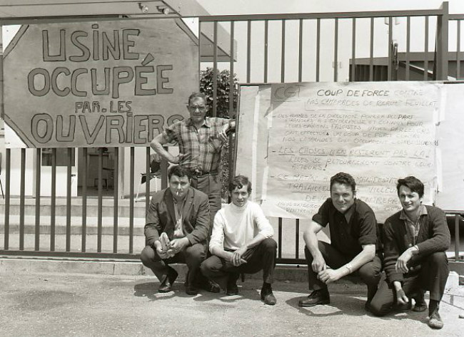 "Strikers in Southern France with a sign reading ""Factory Occupied by the Workers."" Behind them is a list of demands, June 1968 / Public Domain"