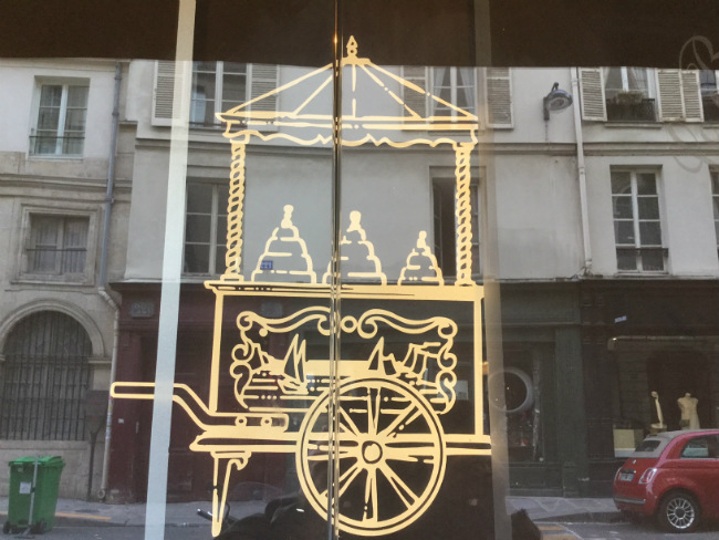 a reflection of an ice cream chariot in a shop window